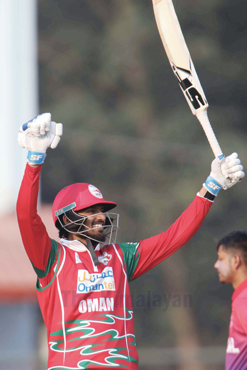 Aqib Ilyas of Oman raises his bat to celebrate a century against host team during the ICC Men's Cricket World Cup League 2 Tri nations series at TU Cricket Stadium in Kathmandu on Sunday. Photo: Udipt Singh Chhetry