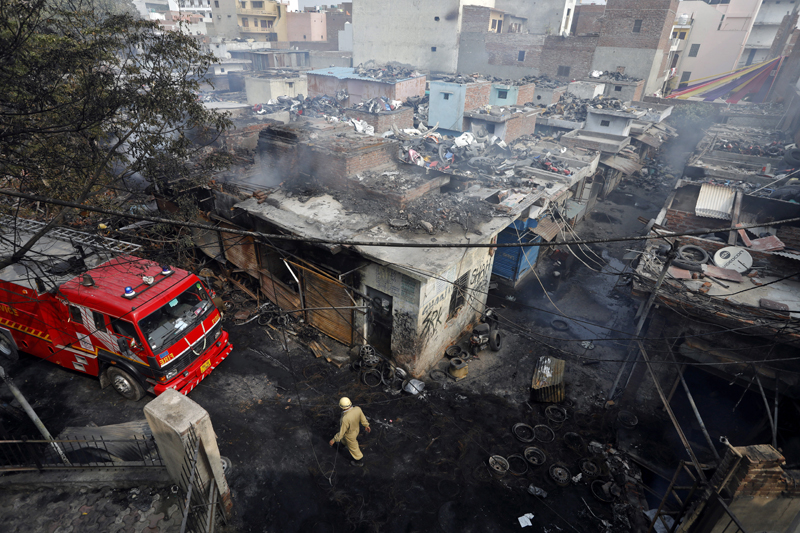 A firefighter walks past damaged shops at a tyre market after they were set on fire by a mob in a riot affected area after clashes erupted between people demonstrating for and against a new citizenship law in New Delhi, India, February 26, 2020. Photo: Reuters