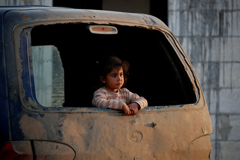 An internally displaced Syrian girl inspects the area from a broken window of a van in an IDP camp located near Idlib, Syria February 27, 2020. Photo: Reuters
