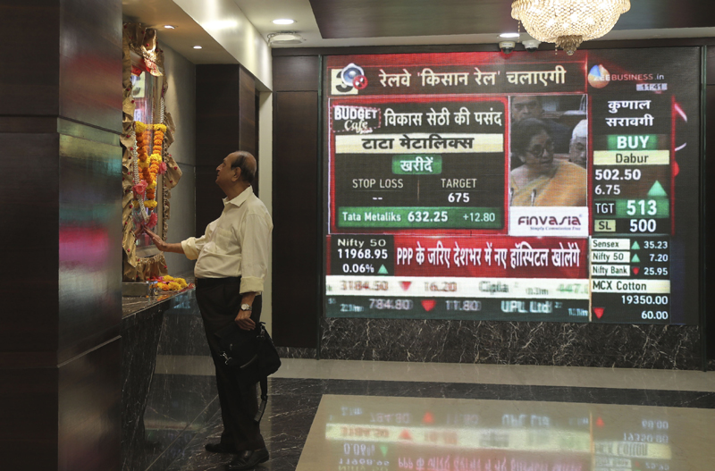 A man offers prayers to a Hindu goddess at the Bombay Stock Exchange (BSE) office, as India's Finance Minister Nirmala Sitharaman is seen on a television screen presenting the annual budget in Mumbai, India, Saturday, Feb 1, 2020. Photo: AP