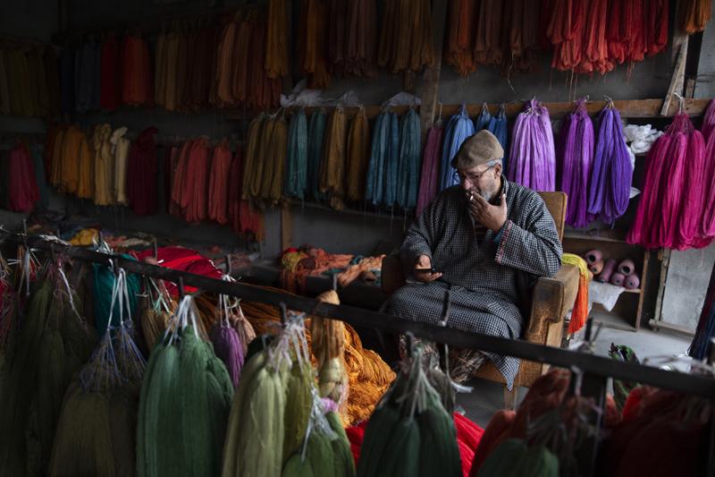 Kashmiri shopkeeper Mohammad Ashraf browses the internet on his mobile phone in  Srinagar, Indian controlled Kashmir, Jan 30, 2020. Photo: AP