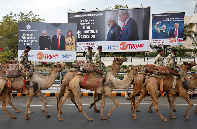Border Security Force (BSF) soldiers ride their camels past hoardings with the images of India's Prime Minister Narendra Modi, US President Donald Trump and first lady Melania Trump, as they take part in a rehearsal for a road show ahead of Trump's visit, in Ahmedabad, India, February 21, 2020. Photo: Reuters