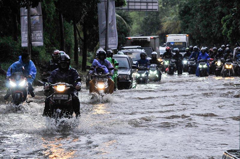 People ride motorcycles along a flooded street in Bekasi, near Jakarta, Indonesia February 25, 2020.Photo:  Antara Foto via Reuters