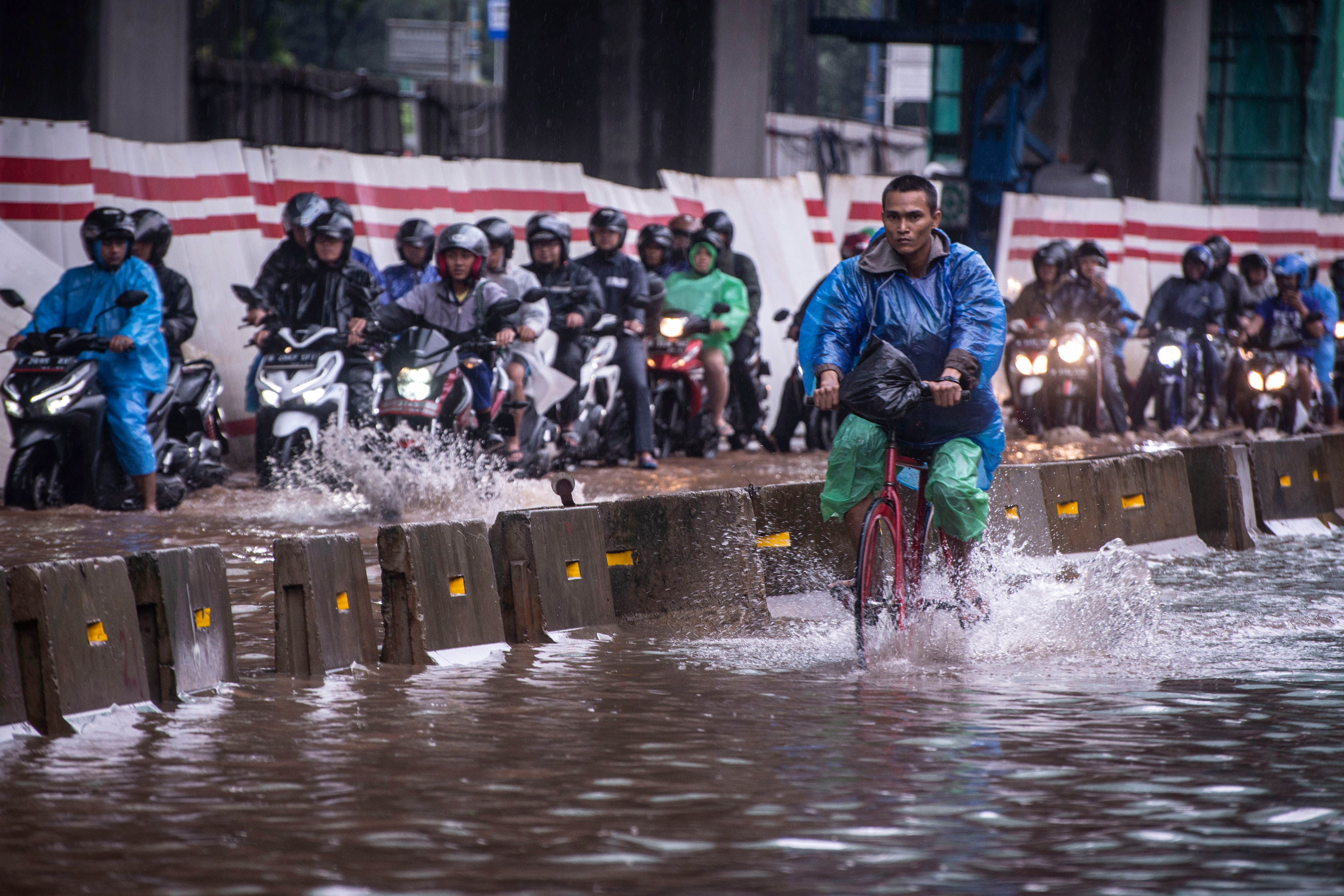 A cyclist rides alongside motorcyclists along a flooded street in Jakarta, Indonesia, February 25, 2020 in this photo taken by Antara Foto. Photo: Reuters