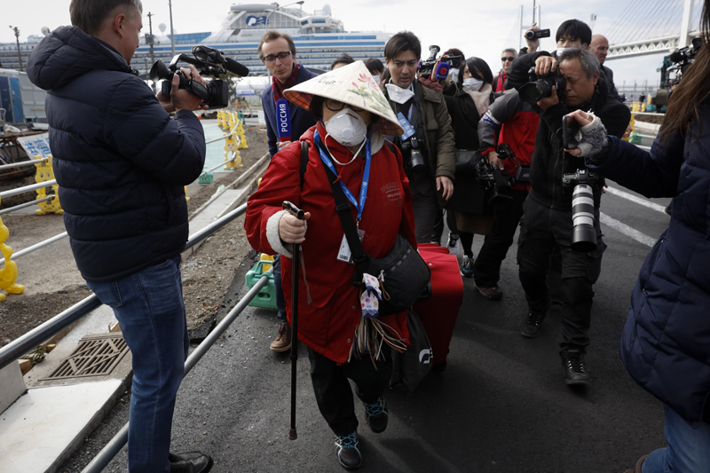 An unidentified passenger is surrounded by the media after she disembarked from the quarantined Diamond Princess cruise ship Wednesday, Feb 19, 2020, in Yokohama, near Tokyo. Photo: AP