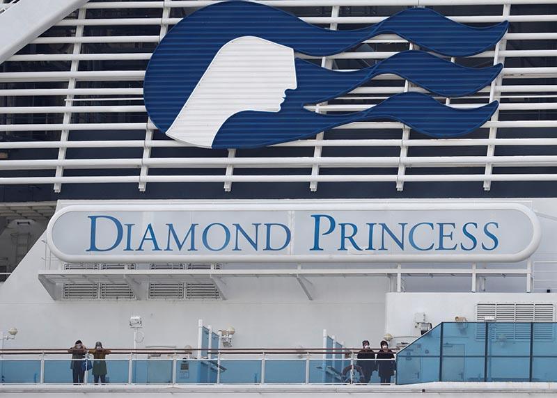 Masked passengers look on from on board the coronavirus-hit Diamond Princess cruise ship docked at Yokohama Port, south of Tokyo, Japan, February 20, 2020. Photo: Reuters