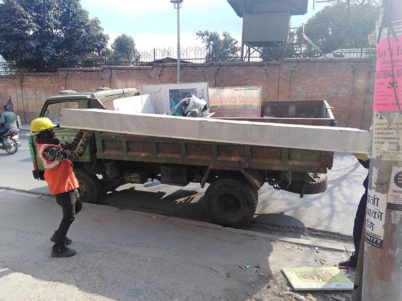 Kathmandu Metropolitan City workers loading hoarding boards onto a vehicle in Anamnagar, Kathmandu, on January 30, 2020. Photo: Sandeep Sen/ THT Online