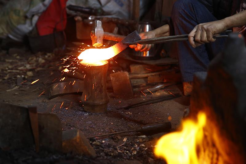 A blacksmith hammers a 'khukuri' (traditional weapon) at Gurkha Khukuri Workshop, in Kathmandu, on Tuesday, February 25, 2020. Photo: Skanda Gautam/THT