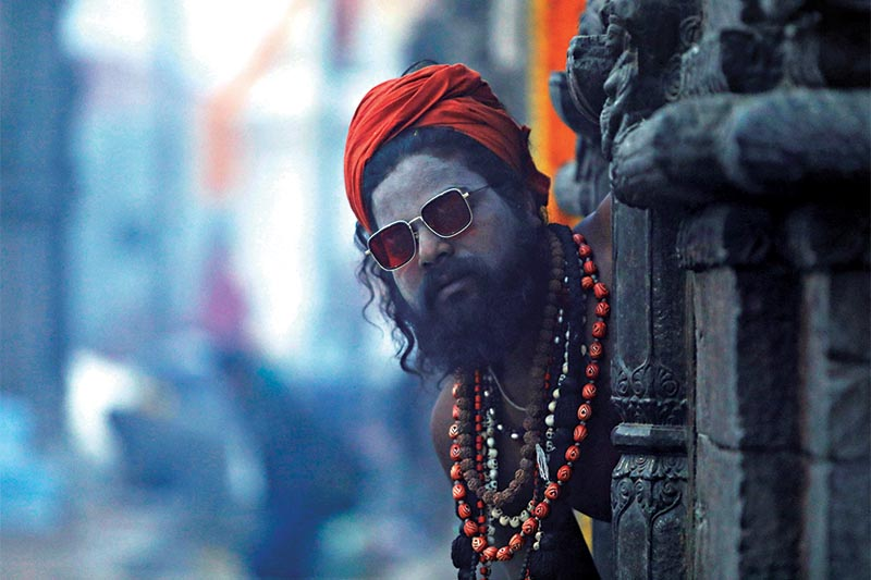 A sadhu looking through a temple on the premises of Pashupatinath temple during Mahashivaratri, in Kathmandu,  on Friday, February 21, 2020. The festival is also celebrated during night by keeping a night-long vigil as it is believed that lord Shiva saved the universe from darkness and ignorance. Photo: AFP