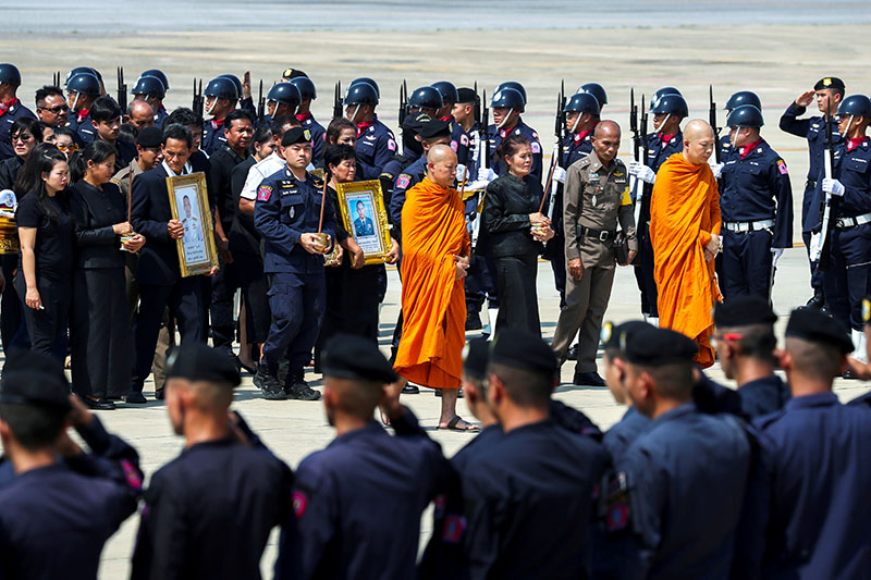 Buddhist monks and families of SWAT members Trakool Tha-arsa and Petcharat Kamjadpai who were killed in a mass shooting at the Terminal 21 shopping mall, are seen at a military airport in Bangkok, Thailand, February 10, 2020. Photo: Reuters