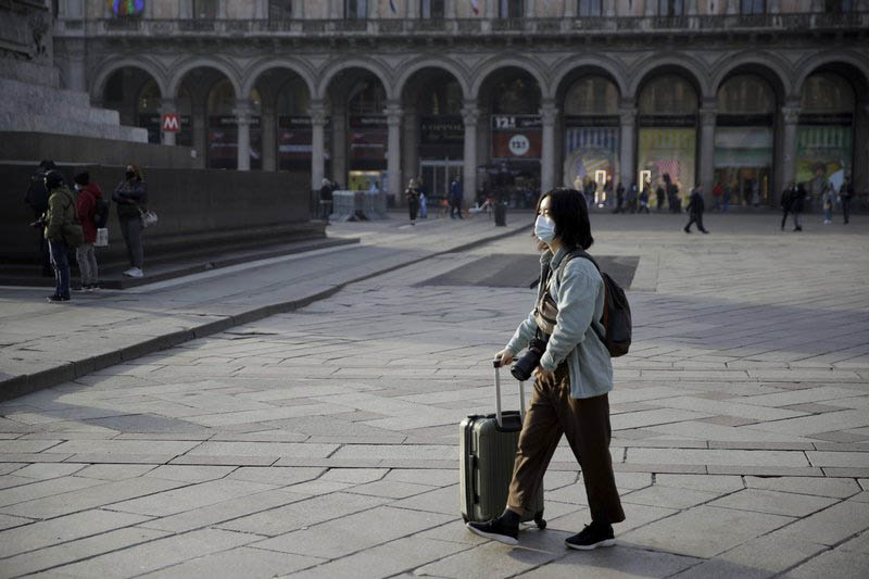A woman wearing a sanitary mask pushes a trolley in Duomo square, Milan, Italy, Sunday, Feb. 23, 2020. Photo: AP