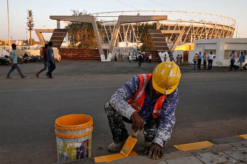 A worker paints footpath in front of Sardar Patel Gujarat Stadium, where US President Donald Trump is expected to visit during his upcoming trip to India, in Ahmedabad, India, February 14, 2020. Photo: Reuters