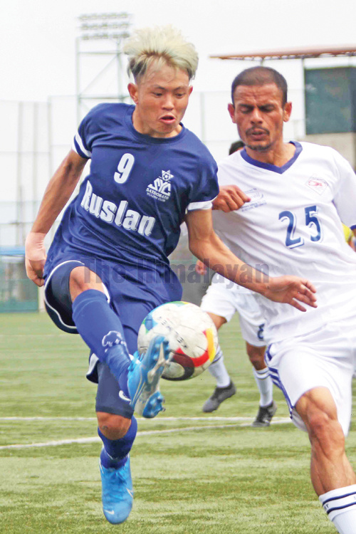 Birendra Limbu (left) of Satdobato Youth Club vies for the ball against Basanta Ojha of Nayabasti Yuva Club during their Martyr's Memorial A Division League match at ANFA grounds in Lalitpur on Tuesday. Photo: THT
