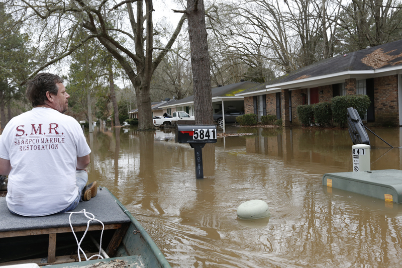 Chris Sharp studies the water damage from the Pearl River that floods his neighborhood in Jackson, Mississippi, Sunday, Feb 16, 2020. Photo: AP