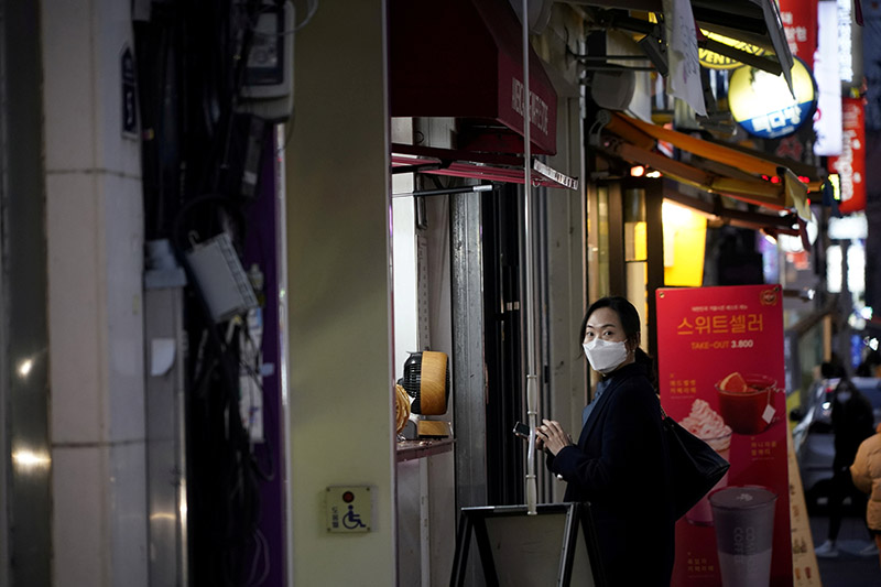 A woman wearing a mask to prevent contracting the coronavirus waits for her food at Dongseong-ro shopping street, in central Daegu, South Korea, on February 21, 2020. Photo: Reuters