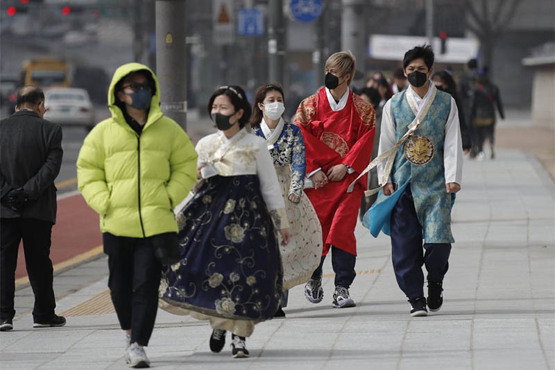 Visitors wearing face masks walk near the Gwanghwamun, the main gate of the 14th-century Gyeongbok Palace, and one of South Korea's well-known landmarks, in Seoul, South Korea, Saturday, Feb. 22, 2020. Photo: AP
