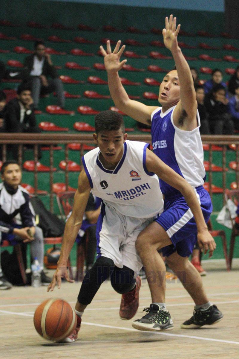 Samriddhiu2019s Rajwol Maharjan (left) drives the ball past Ramechhap player during their IIMS fifth Under-18 National Basketball Tournament match in Kathmandu on Monday. Photo: THT