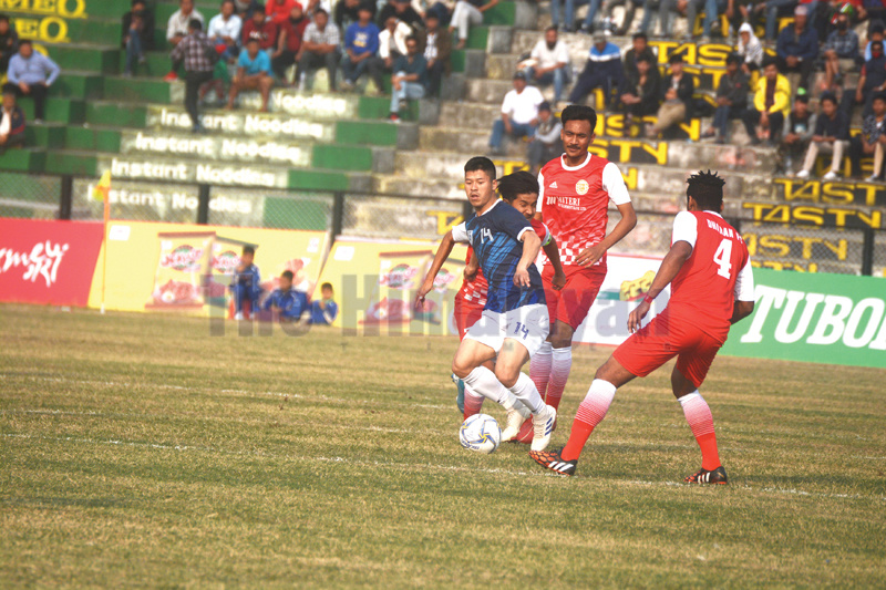 Wangden Tamang of United Kurseong FC vies for the ball with Dharan FC players during the inaugural match of the 22nd Budhasubba Tuborg Gold Cup in Dharan, on Saturday. Photo: THT