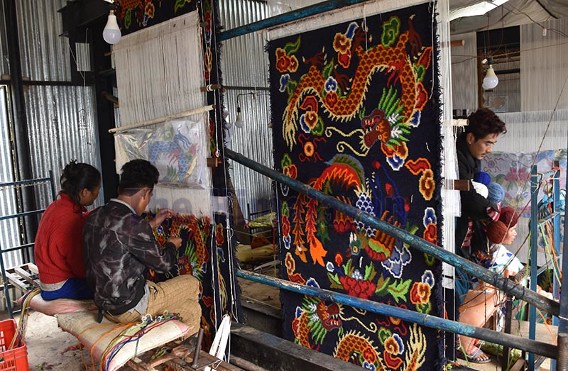 Workers weaving a blanket on a traditional loom in a factory in Nilkantha Municipality, Dhading, on Saturday. The factory is run by a local cooperative in the district. Photo: THT