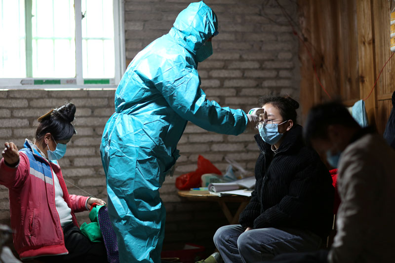 A medical worker in protective suit takes body temperature measurement of a villager as the country is hit by an outbreak of the new coronavirus, in Danzhai county, Qiandongnan Miao and Dong Autonomous Prefecture, Guizhou province, China January 31, 2020. Photo: Reuters