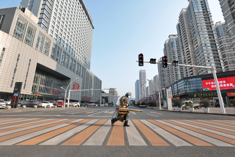 A worker with sanitizing equipment crosses the road in front of a hospital in Yichang city of Hubei, the province hit hardest by the novel coronavirus outbreak, China February 12, 2020. Picture taken February 12, 2020. China Daily via Reuters