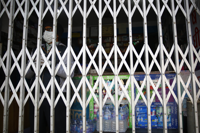 A pharmaceutical staffer stands inside a pharmacy on the third day of the nationwide lockdown amid concerns over the spread of coronavirus infection (COVID-19), in Lalitpur, on Thursday, March 26, 2020. Photo: Skanda Gautam/THT