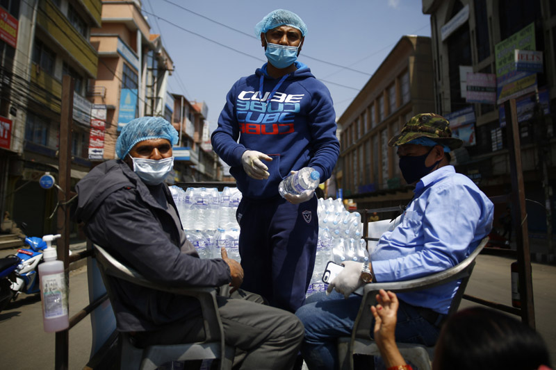 Drinking water for the public is distributed from a vehicle along the city street on the third day of the nationwide lockdown, in Lalitpur, on Thursday, March 26, 2020. Photo: Skanda Gautam/THT