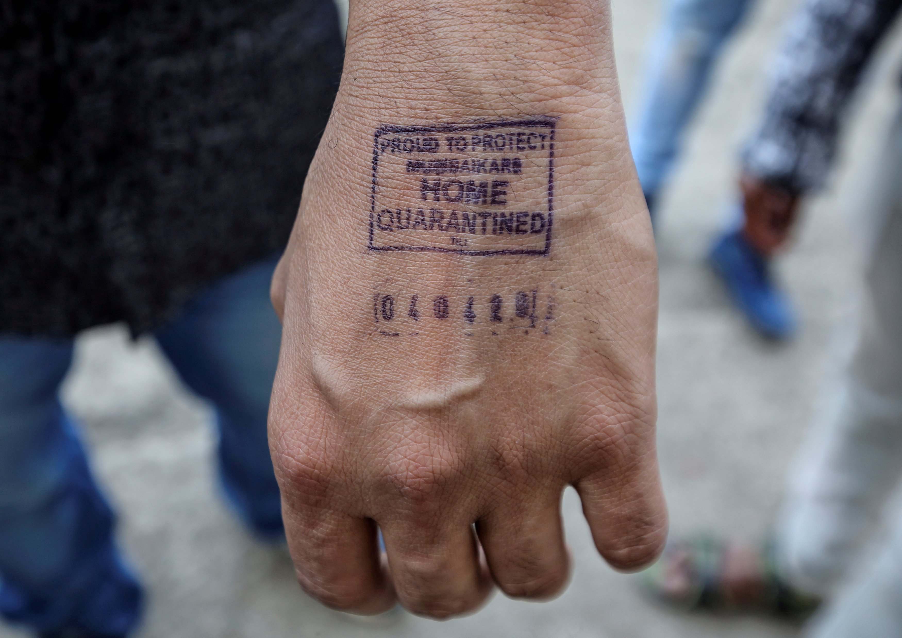 FILE - A man shows his hand which was stamped by airport authorities as he was advised for home quarantine after he arrived from overseas, amid coronavirus disease (COVID-19) fears, in Mumbai, India, March 21, 2020. Photo: Reuters