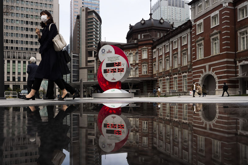 A countdown clock for the Tokyo 2020 Olympics is reflected in a puddle of water outside Tokyo Station in Tokyo, Monday, March 23, 2020. Photo: AP