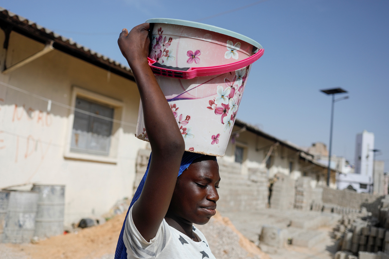 A girl carries a bucket of clean water in Pikine on the outskirt of Dakar, Senegal March 9, 2020. Photo: Reuters