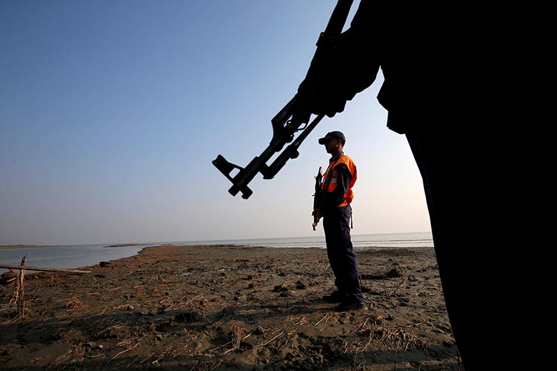 FILE PHOTO: Bangladesh coast guards keep watch in the Thengar Char island in the Bay of Bengal,  Bangladesh, February 2, 2017. Picture taken February 2, 2017. Photo: Reuters