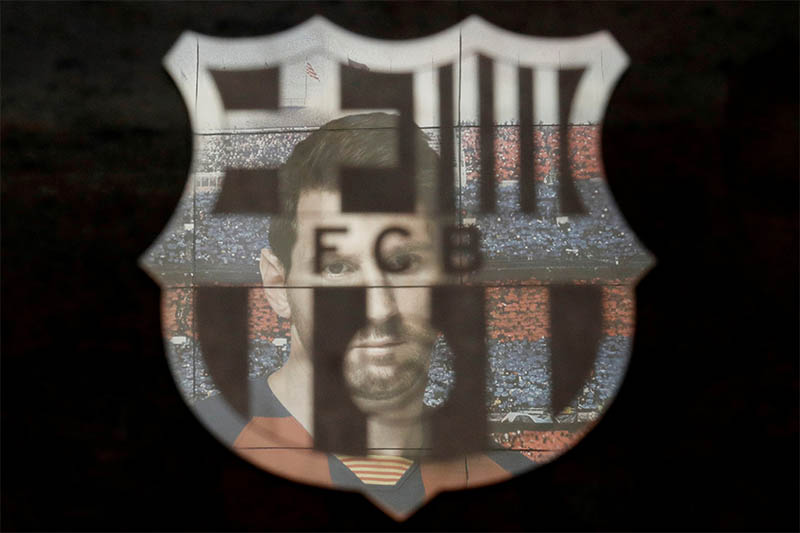 FILE PHOTO: A picture of Lionel Messi is reflected in the Barcelona emblem outside the stadium before the match. Photo: Reuters