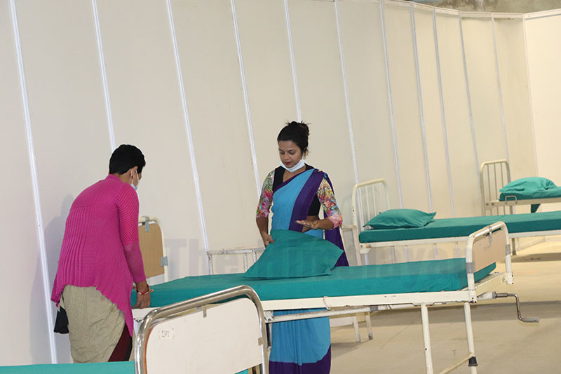 Health workers managing beds at the newly set up Bharatpur Corona Special (Temporary) Hospital to treat patients infected with coronavirus, at Bharatpur, Chitwan, on Friday, March 20, 2020. Photo: Tilak Ram Rimal/THT