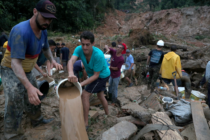 Residents carry buckets of mud and water, as firefighters (not pictured) dig for victims of a mudslide, where people remain missing at Barreira neighbourhood in Guaruja, Sao Paulo state, Brazil, March 3, 2020. Photo: Reuters