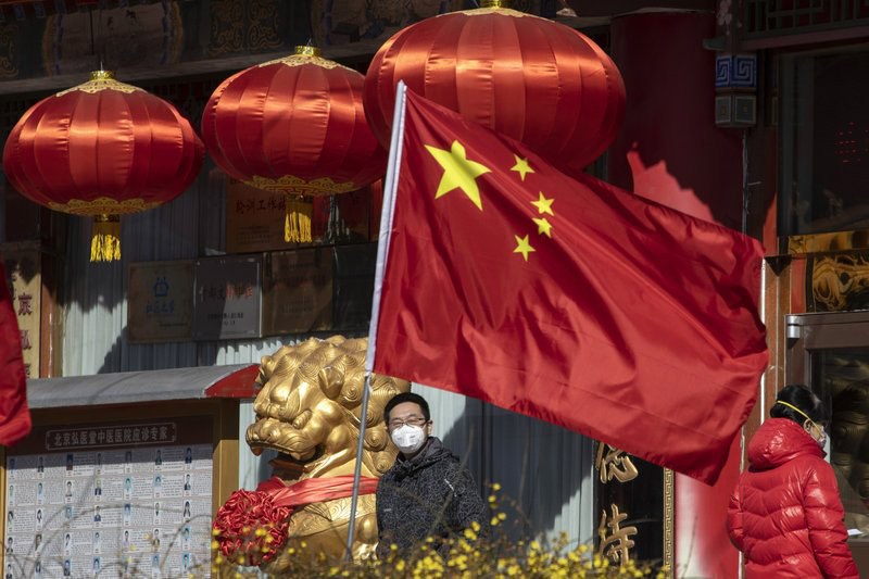 A masked man looks out near a national flag outside a traditional medicine hospital in Beijing, on Tuesday, March 3, 2020. Mushrooming outbreaks in the Mideast, Europe and South Korea contrasted with optimism in China, where thousands of recovered patients were going home and new virus cases drop to a new low. Photo: AP