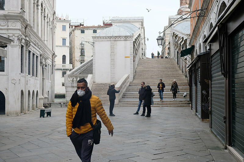 A man wearing a protective face mask walks through a street after the Italian government imposed a virtual lockdown on the north of Italy including Venice to try to contain a coronavirus outbreak, in Venice, Italy, on March 9, 2020. Photo: Reuters