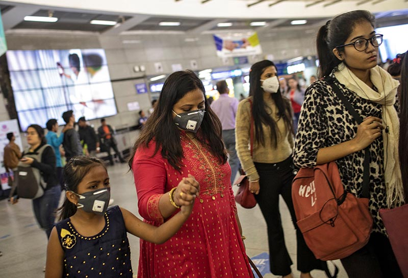 Commuters wearing protective masks rush to board metro trains at a station, amid coronavirus disease (COVID-19) fears, in New Delhi, India, on Friday, March 13, 2020. Photo: Reuters