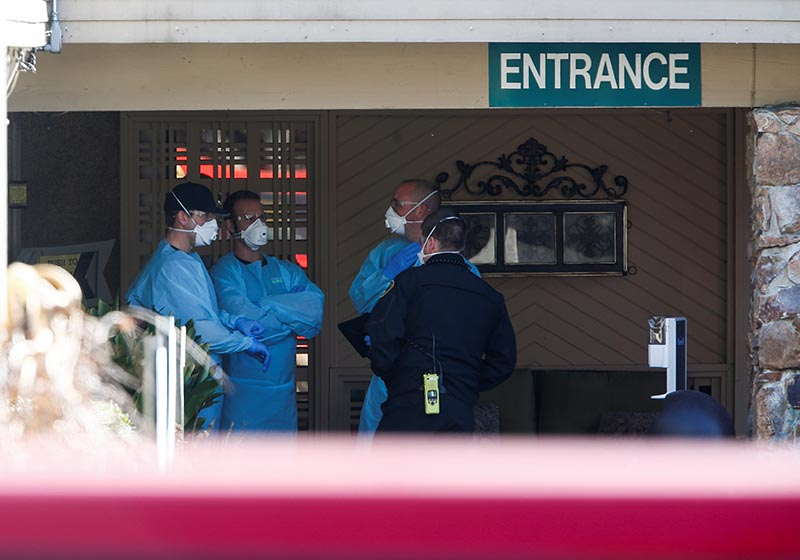 Medics in disposable gowns and masks talk outside the Life Care Center of Kirkland, a long-term care facility linked to several confirmed coronavirus cases, in Kirkland, Washington, US March 4, 2020. Photo: Reuters