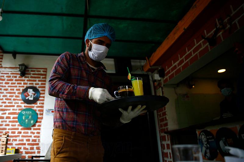 A waiter wearing a protective face mask and gloves serves customers amid concerns over the coronavirus spread in Kathmandu, on Sunday, March 22, 2020. Photo: Skanda Gautam/THT