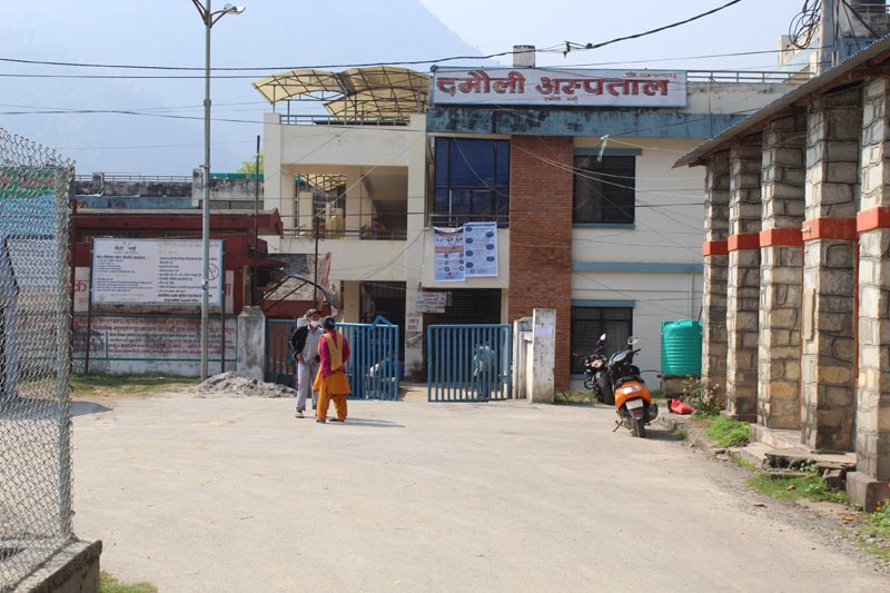Two persons are seen standing in front of Damauli Hospital in Tanahun district, on Tuesday, March 31, 2020. Photo: Madan Wagle/ THT