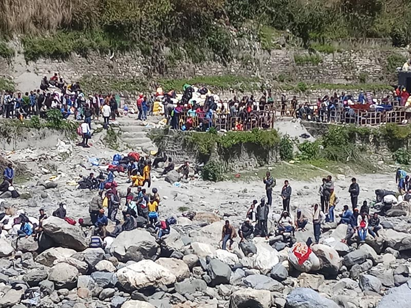 Stranded Nepalis are seen sitting at the bank of Mahakali River in Dharchula of India, across the Nepal-India border, as pictured from Darchula district in Nepal. Photo Courtesy: Narendra Karki