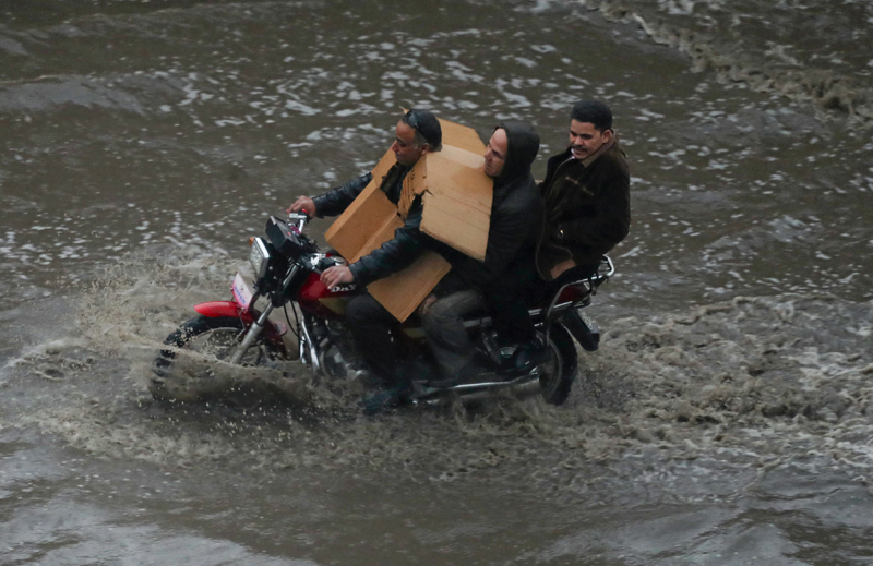 A man with cartoon cover rides a motorbike during a thunderstorm and heavy rains in Cairo, as the government announced a day off while the rain exceeds the infrastructure's capacity in most cities, Egypt March 12, 2020. Photo: Reuters