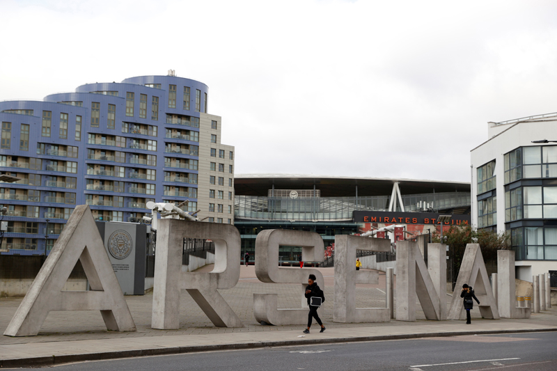People walk outside the Emirates Stadium, London, Britain, March 13, 2020. Photo: Action Images via Reuters/John Sibley