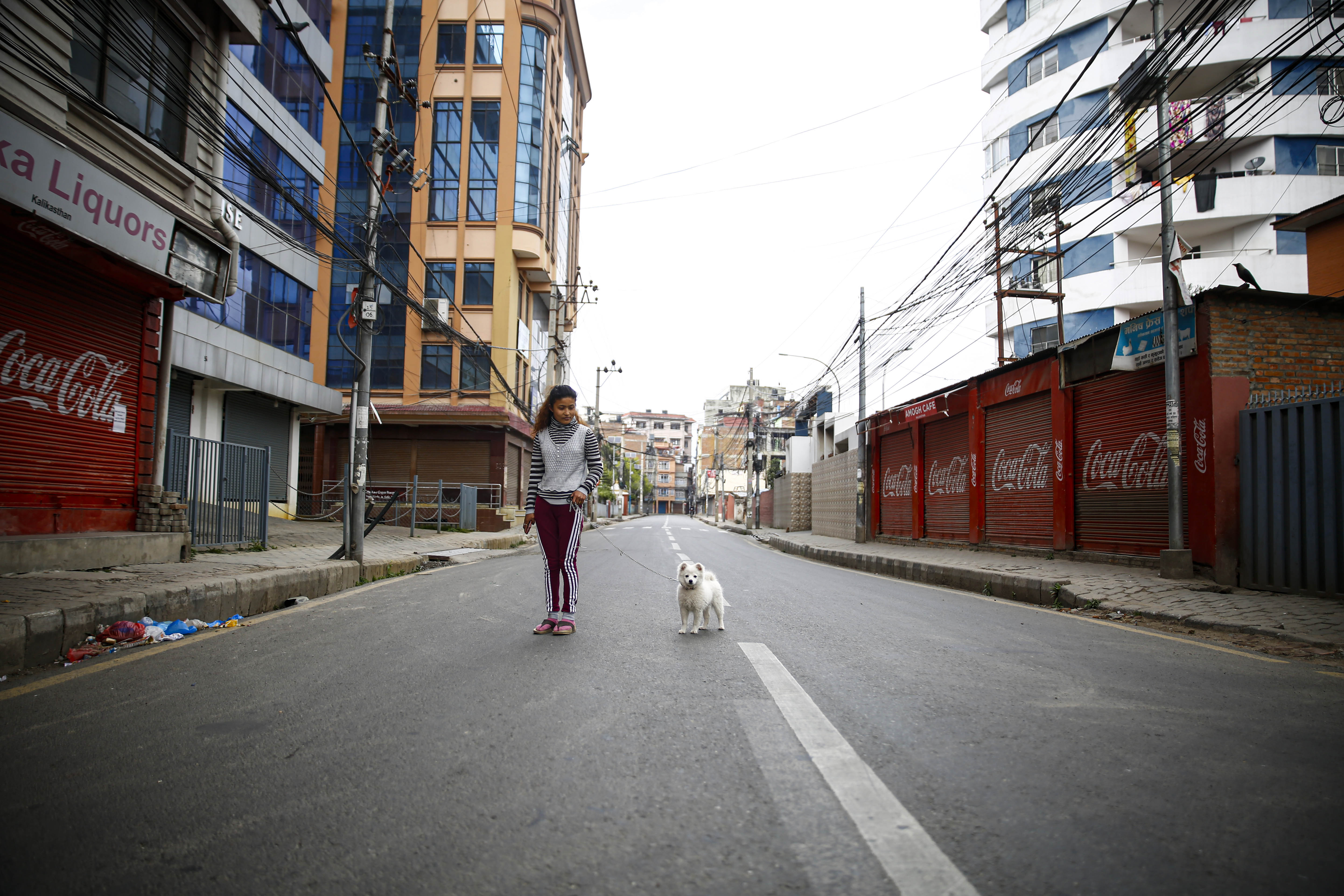 A woman and her dog walk on the empty road after the government imposed a nationwide lockdown for a week in an effort to control the possible spread of COVID-19 after Nepal confirmed the second case of a 19-year-old Nepali student, who had returned from France via Qatar, in Kathmandu, on Tuesday, March 24, 2020. Photo/Skanda Gautam/THT