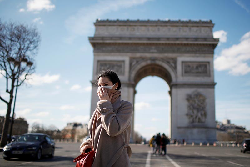 A woman wearing a protective mask, walks near Arc de Triomphe following France's Prime Minister announcement to close most all non-indispensable locations, cafes, restaurants, cinemas, nightclubs and shops as France grapples with an outbreak of coronavirus (COVID-19) disease, in Paris, France, March 15, 2020. Photo: Reuters