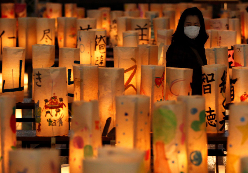 A woman wearing a mask looks at paper lanterns created at a memorial for the victims of the March 11 earthquake and tsunami in Koriyama, Fukushima prefecture March 10, 2012, a day before the one-year anniversary of the disaster. Photo: Reuters/File
