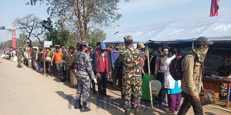 Security personnel are seen monitoring Nepalis returning home from India, waiting in a queue for health screening, at Gadda Chowki border transit point, in Kanchanpur district, on Friday, March 21, 2020. Photo: Tekendra Deuba/THT
