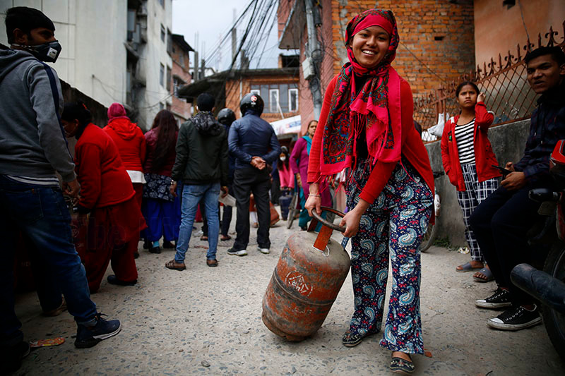 A woman smiles as she collects an LPG cylinder from a nearby depot in Anamnagar, Kathmandu, on March 22, 2020. Photo: Skanda Gautam/THT