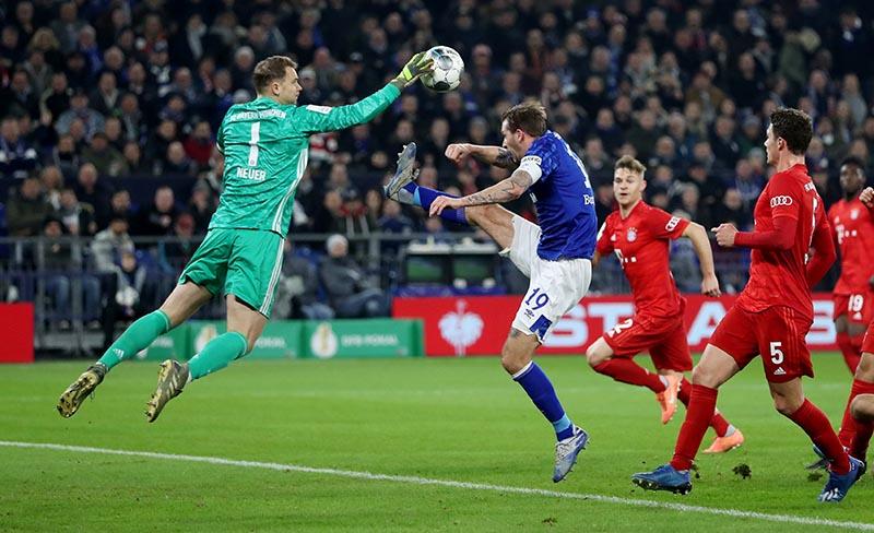 Schalke 04's Guido Burgstaller in action with Bayern Munich's Manuel Neuer during the DFB Cup match between Schalke 04 and Bayern Munich, on Veltins-Arena, in Gelsenkirchen, Germany, on March 3, 2020. Photo: Rueters