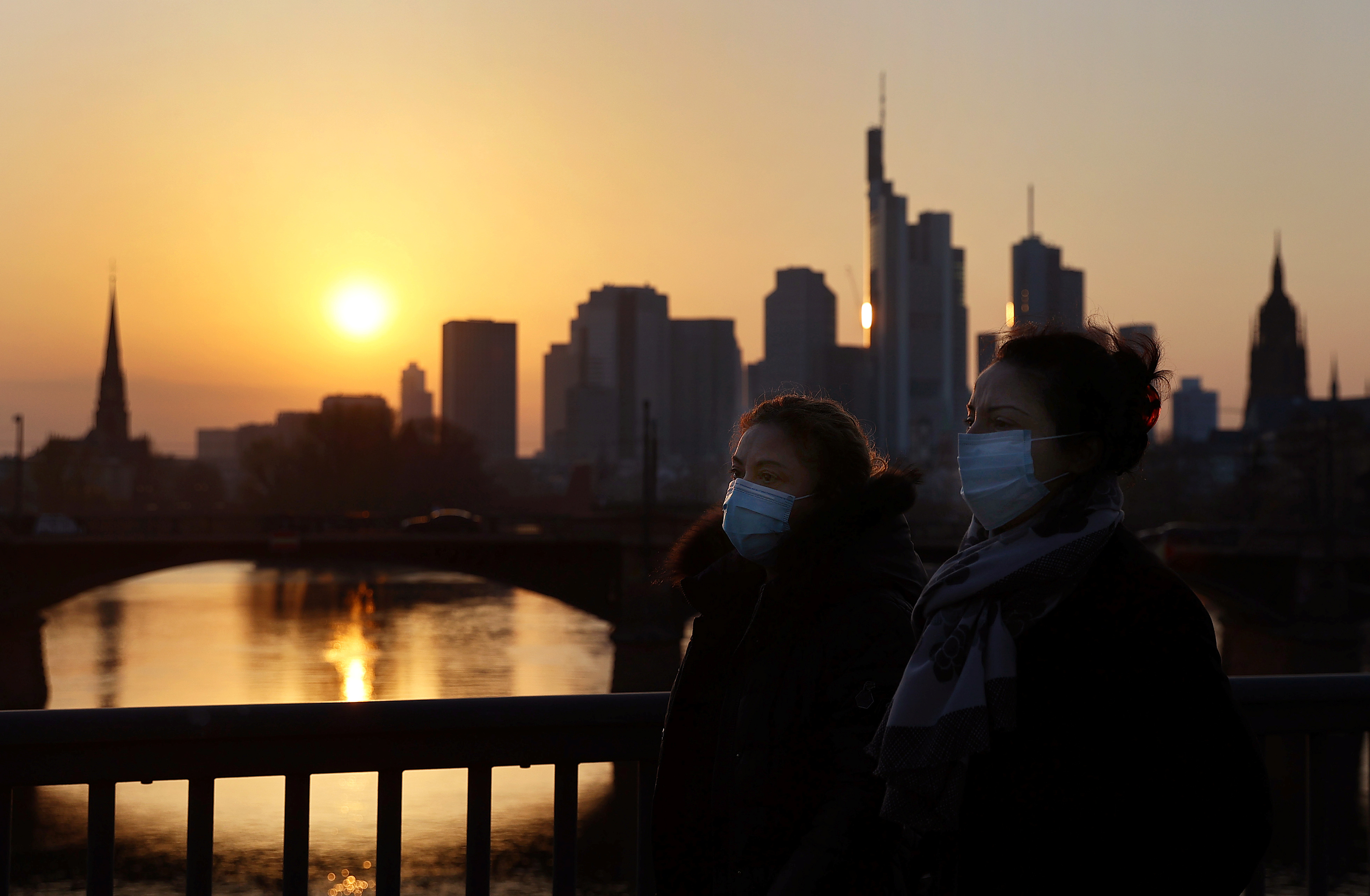 Two women wearing protective masks cross a bridge in front of the skyline in Frankfurt, Germany, March 28, 2020, as the spread of the coronavirus disease (COVID-19) continues. Photo: Reuters